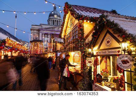 NOTTINGHAM ENGLAND - DECEMBER 22: Man making purchase at Nottingham Christmas Market. In Nottingham England. On 22nd December 2016.
