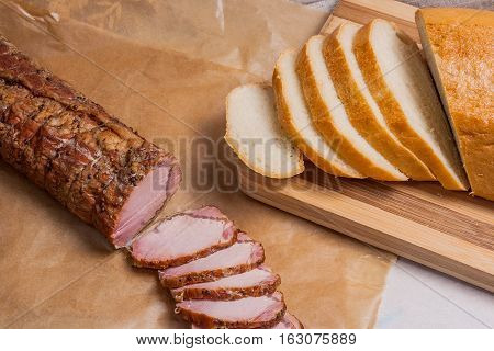 Slices Smoked Meat Or Ham On Brown Packing Paper. Slices White Wheat Bread On Wooden Cutting Board.