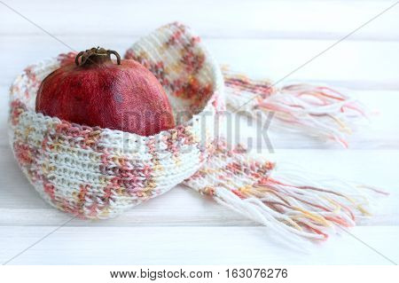 pomegranate fruit wrapped in a warm scarf warming / winter fruit diet