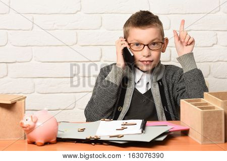 young cute businessboy in grey sweater and glasses sitting at table with papers pink piggy pig bank holding and speaking on cell phone on white brick wall background copy space