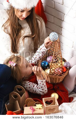 young cute little blonde girl in christmas red dress lying on her mothers lap in xmas hat and long brunette hair and holding basket with new year colorful balls on white brick wall background