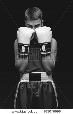 Young handsome boxer sportsman in white boxing gloves on black backgound. Copy space. Monochrome photo.