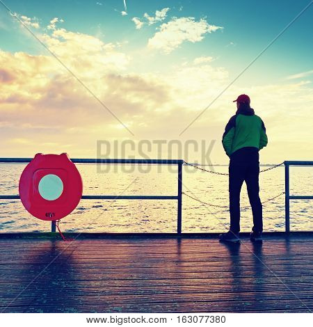 Alone Man On Pier And Look Over Handrail Into Water. Sunny Sky, Smooth Water Level