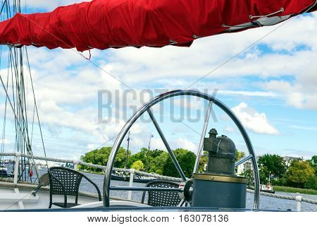 Steering wheel and red sails of the tall ship against a blau sky. Sailing ship detail. Concepts: prosperity, optimism, positive, future