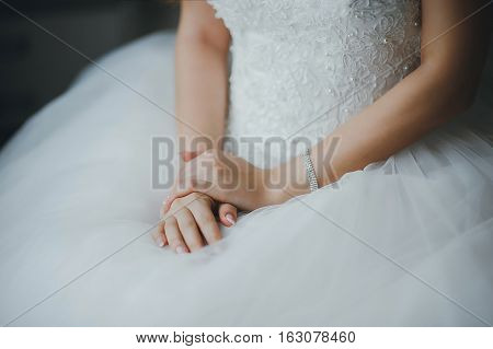 Fees bride. Bride in wedding dress sits on a chair. Hands close-up