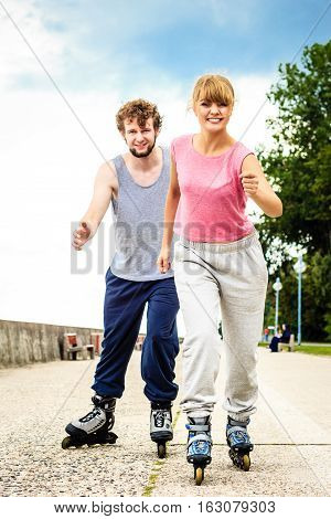 Active young people friends in training suit  outdoor. Happy woman and man riding enjoying sport.