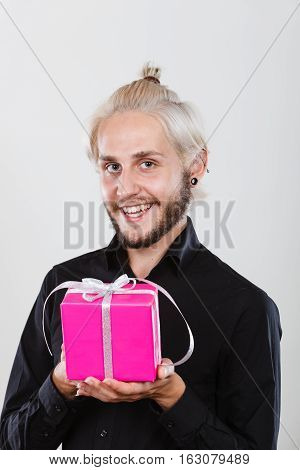 People celebrating xmas love and happiness concept - cool young man holding present pink gift box in hand