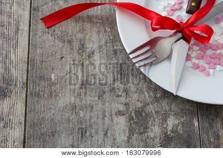 Valentine Dinner. Valentine candies with heart shape on a white plate, knife and fork on wooden table.