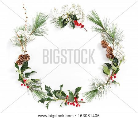 Frame from pine tree branches with ilex leaves on white background. Christmas floral flat lay