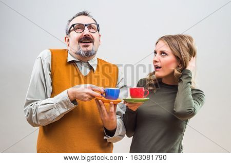 Funny nerdy man and beautiful woman enjoy talking and drinking coffee.