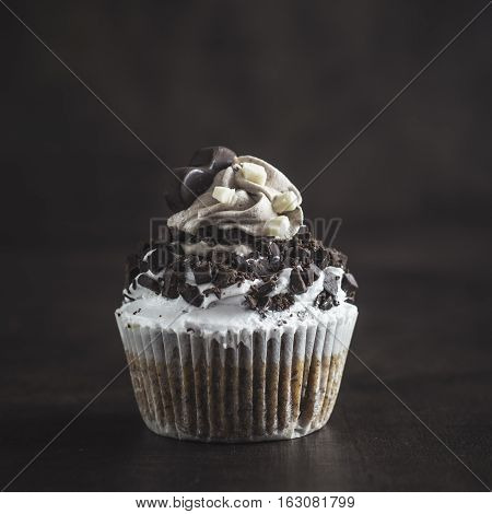 Chocolate cupcake on wooden background, close up