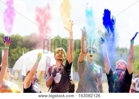 Young people having fun during Holifest throwing colorful powder in the air