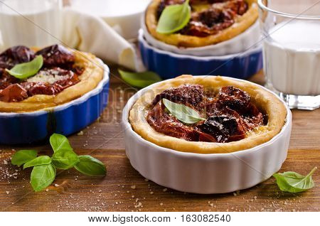 Open pies with dried tomatoes on a wooden background. Selective focus.
