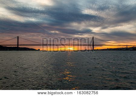 Sunset sky above Tagus River, Bridge April 25 Lisbon and Lisbon port at from ship, Portugal.