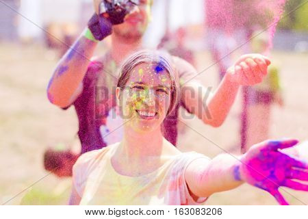 Girl and guy stained with colorful powder having fun during Holifest