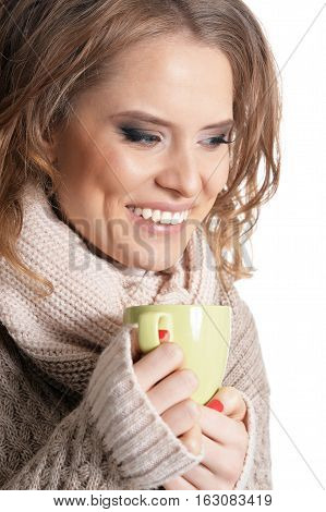 beautiful young girl drinking tea, against white background