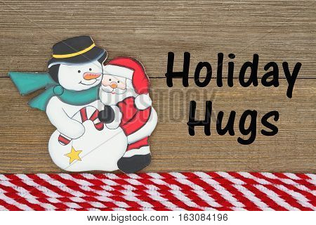 Old fashion Christmas greeting A retro snowman hugging Santa Claus on weathered wood background with text Holiday Hugs
