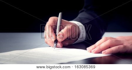 Businessman Signing An Official Document  On Dark Background