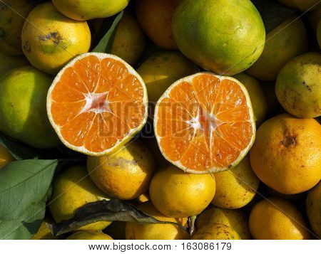 One tangerine cut in two perfect halves. On a stand of a street fruit market.