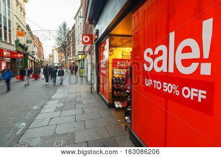 NOTTINGHAM ENGLAND - DECEMBER 26: Big red Boxing Day sales poster and shoppers on Clumber Street in Nottingham. In Nottingham England. On 26th December 2016.