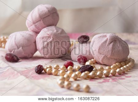 marshmallows home on a color background with a delicate casket from porcelain and berries and pearls