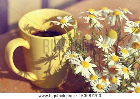 Black coffee in yellow mug and a bouquet of field daisies on a sunny day / coffee break in the fresh air