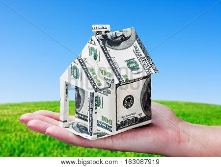 House made of money in hand on background of green field