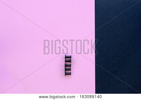 thumbtacks pinned arrange to symbolize to be different or leadership with copy space on pink and black textured background. Close up. Flat lay