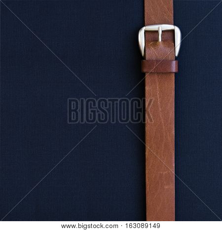 Leather belt with a buckle on black textured background. Flat lay. Top view