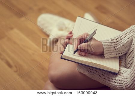 Detail of a young woman holding a planner and writing in her diary enjoying winter days in a cozy home atmosphere