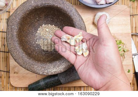 Chef putting garlic to mortar/ cooking fried chicken wings concepted