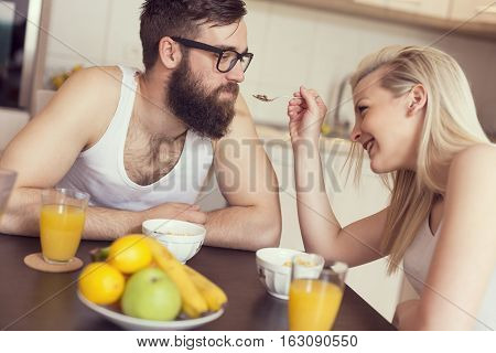 Couple in love sitting at a kitchen table having a breakfast together girl feeding the guy. Focus on the guy