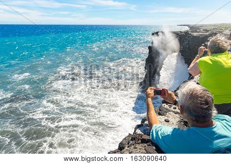 Tourists photographing Holei Sea Arch in Volcanoes National Park, Big Island, Hawaii, Usa