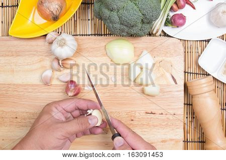 Chef is peeling garlic / coking spicy spaghetti concept