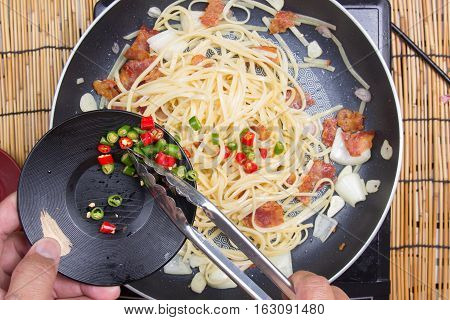 Chef putting slice of chili for cooking/ cooking spicy spaghetti concept