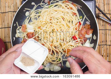 Chef putting salt for cooking / cooking spicy spaghetti concept