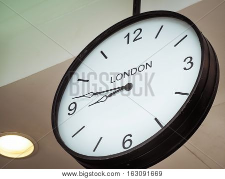 An airport clock showing London time zone at 9 past 45, Retro filter color