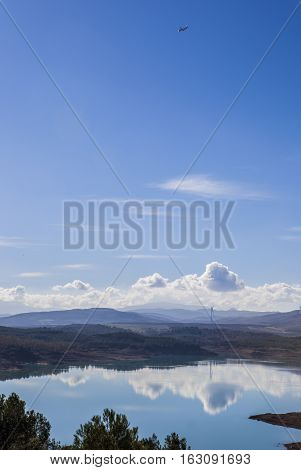 El Chorro reservoir landscape with windmills at bottom and aircraft in the sky Malaga Spain