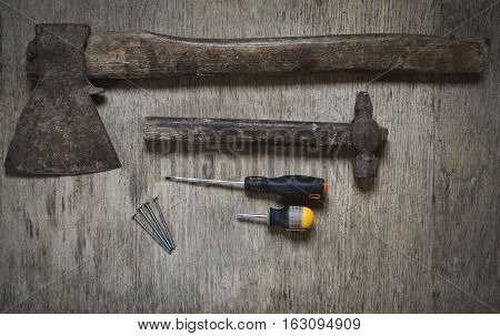 ax, a hammer, a screwdriver and nails. worker abstract on the wooden tavle