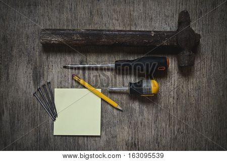 ax, a hammer, a screwdriver and nails. worker abstract and blank with pencil