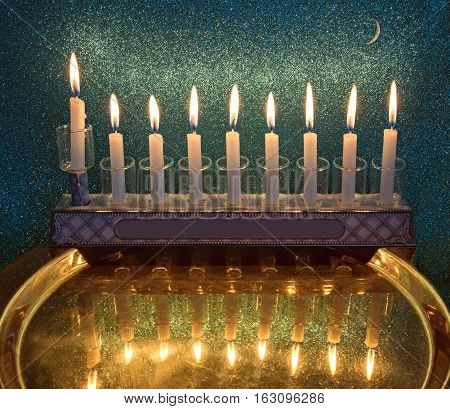 Composite image with menorah of burning lights of candles and crescent moon on glitter background