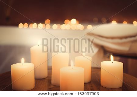 Close up of candles fire on small table. Bed for massage on background