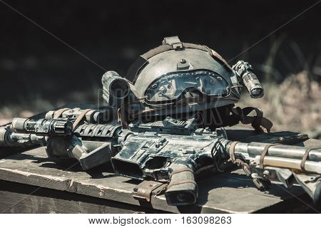 The machine machine gun army helmet with a flashlight lying in a pile on a wooden box of ammunition. Conducting military operations.