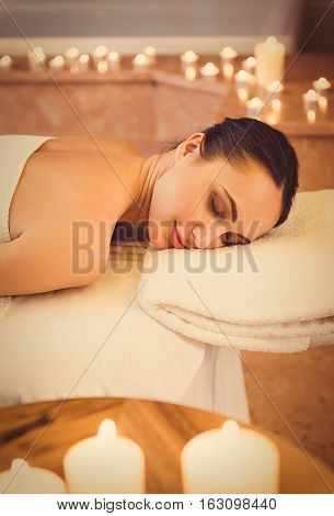 Tranquil young woman is lying on massage bed near burning candles at beauty salon. Her eyes are closed with pleasure