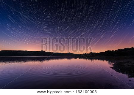 Star Trails Above Ripples On A Calm Lake In Corsica At Sunrise