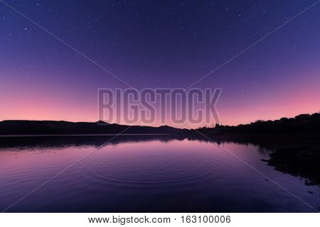 Ripples On A Lake At Sunrise With Star Filled Purple Sky