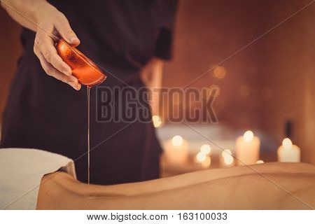 Relax and get some pleasure. Close up of masseuse hands holding jar and pouring oil on female back