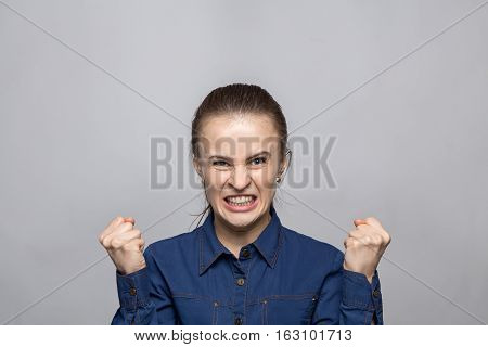 Portrait of enraged woman on gray background
