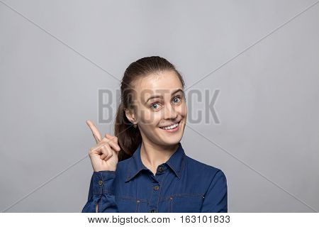 Portrait of woman with forefinger on gray background