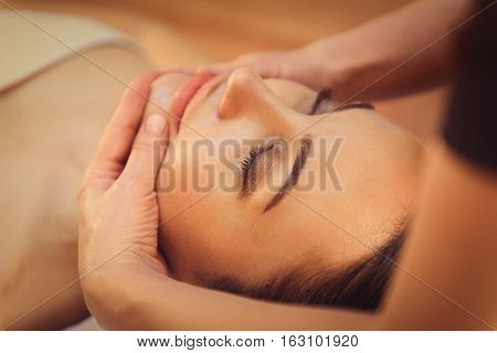 Close up of masseuse hands massaging female face with gentleness. Peaceful girl closed eyes with enjoyment